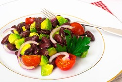 Salad with avocado, beans, cherry tomatoes, red onion and vegetable oil. Studio Photo