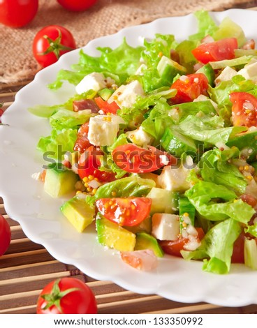 Salad with avocado, cherry tomatoes and mozzarella with honey-bacon dressing