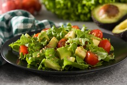 Salad with avocado, lettuce, tomato and flax seeds on gray background.Close up