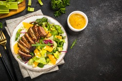 Salad with baked duck, green salad mix and oranges.
