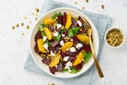 salad with beet, curd, avocado, orange, feta, ricotta and pumpkin seeds, keto ketogenic dash diet, modern and pastel background, top view