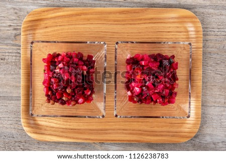 Salad with beets. Vinegret is a traditional Russian salad made from beets and vegetables in a transparent bowl. Background tree. Top view. Copy space. Horizontal shot.