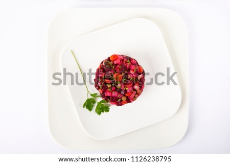 Salad with beets. Vinegret is a traditional Russian salad made from beets and vegetables in a white plate. The background is white. Top view. Copy space. Horizontal shot.