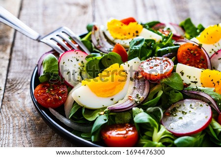 Salad with boiled egg and vegetables on wooden table  Сток-фото ©