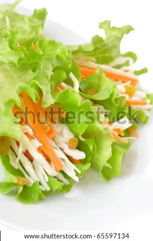 Salad with cabbage, carrots and raisins in a dish closeup