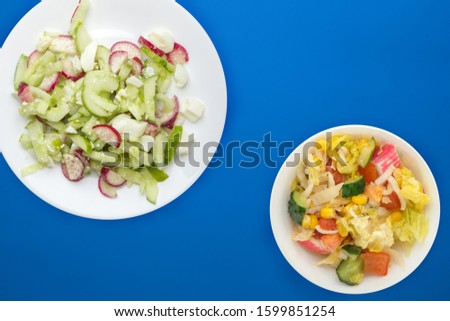 salad with cucumbers and eggs on a white  plate on  blue background .healthy food . vegetarian food top view. Asian cuisine