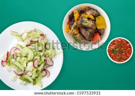 salad with cucumbers and eggs on a white  plate on  green background .healthy food . vegetarian food top view. Asian cuisine