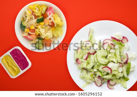salad with cucumbers and eggs on a white plate on red background .healthy food . vegetarian food top view. Asian cuisine
