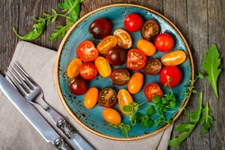 Salad with fresh colorful tomatoes, olive oil, oregano and arugula on plate on wooden table, top view