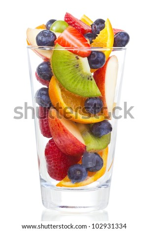 salad with fresh fruits and berries in glass on white background