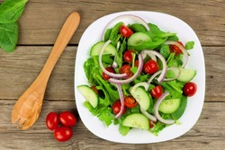 Salad with greens, cherry tomatoes, red onions and cucumber on white plate with wood background, overhead view with fork