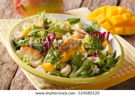 salad with grilled chicken breast, mango, arugula, lettuce, spinach and chicory closeup on the table. horizontal  #524080120