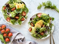 Salad with juicy cherry tomatoes, green and red lettuce, leek, spring and red onion, spices and apples. Homemade food. Symbolic image. Concept for a tasty and healthy vegetarian meal. Close up