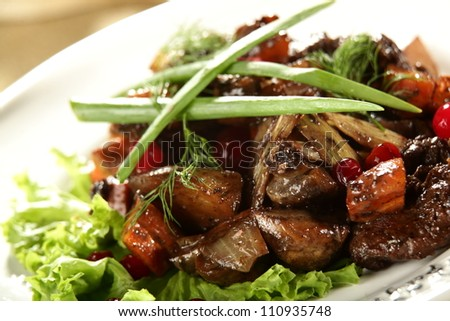 salad with meat and berries on the white dish