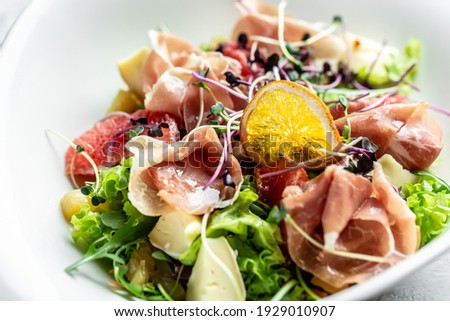Salad with Prosciutto, ham and grapefruit jamon, salad mix, grapefruit, cherry tomatoes, parmesan cheese. Cold snacks. Food recipe background. Close up. Foto stock ©