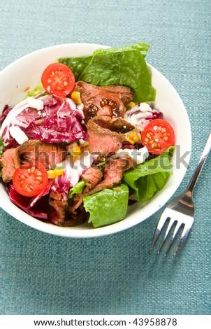 Salad with radicchio, romaine, tomato, corn, tomato and beef