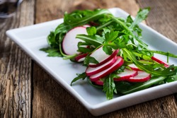 Salad with rucola and radish on  white plate on rustic wooden table