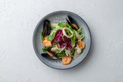 Salad with seafood on white concrete table
