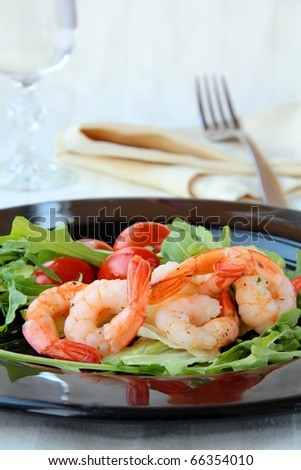 salad with shrimp and tomatoes on a black plate