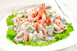Salad with shrimp, avocado, tomatoes and mayonnaise on the lettuce in the plate, napkin, fork on background wooden plank