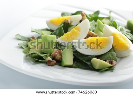 Salad with spinach, avocado, boiled eggs, and walnuts