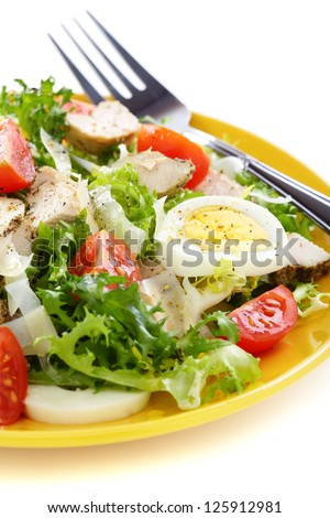 Salad with tomatoes and chicken on a white background.
