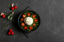 Salad with traditional italian burrata cheese with arugula and tomatoes om dark concrete table with with cooking ingredients cherry tomatoes, basil, garlic and olive oil. Top view. Copy space.