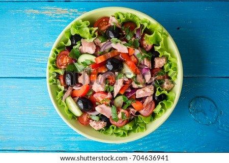 Salad with vegetables and tuna on rustic blue wooden table. Top view.
