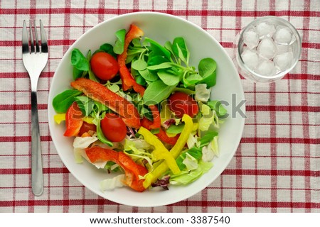 Salad with water glass on tablecloth - high angle view