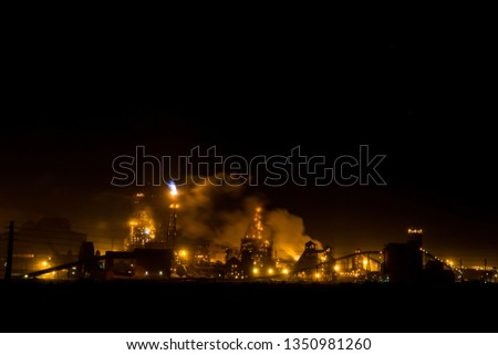 Saladanha Bay coal power station at night with light on and smoke rising of buildings with gas blue flames coming out flare stack is South Africa west coast.  #1350981260