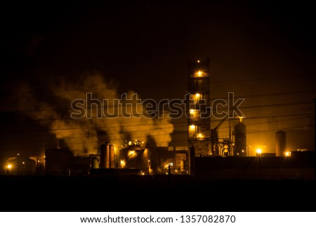 Saladanha Coal power station at night with light on and smoke rising of buildings with gas blue flames coming out flare stack is South Africa west coast.  #1357082870