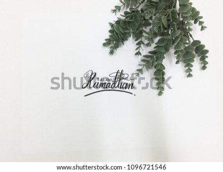 Salam Ramadhan (Ramadhan Greetings) calligraphy on white paper with eucalyptus plant   #1096721546