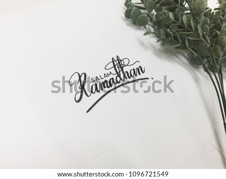 Salam Ramadhan (Ramadhan Greetings) calligraphy on white paper with eucalyptus plant   #1096721549