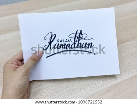 Salam Ramadhan (Ramadhan Greetings) calligraphy on white paper with eucalyptus plant   #1096721552
