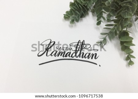 Salam Ramadhan (Ramadhan greetings) calligraphy on white paper with green plant on the right side  #1096717538