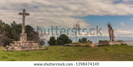 Salamanca, Castilla y Leon, Spain - April 14, 2013: View of a stone cross and the trunk of a tree in a lonely spot of a lonely viewpoint to the mountains