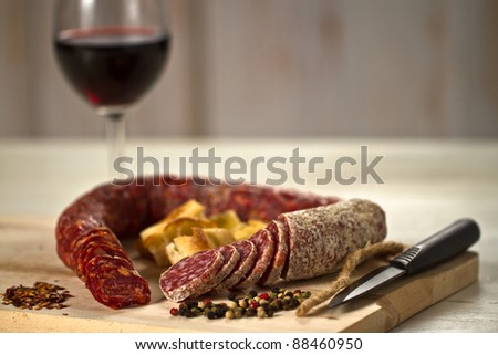 Salami and spicy salami with focaccia pizza decorated with  peppergrain and grounded red pepper over a wooden chunk-board. With a red wine glass on background
