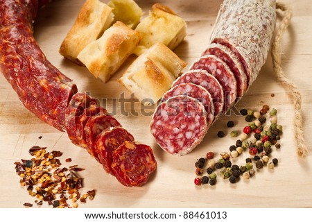 Salami and spicy salami with focaccia pizza decorated with  peppergrain and grounded red pepper over a wooden chunk-board