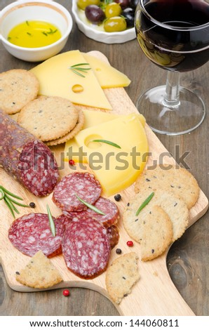 salami, cheese, crackers, olives and a glass of wine on a cutting board vertical