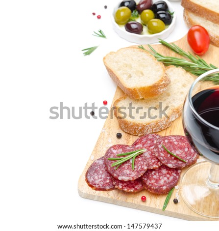 salami, ciabatta, olives and a glass of wine on a wooden board isolated on white