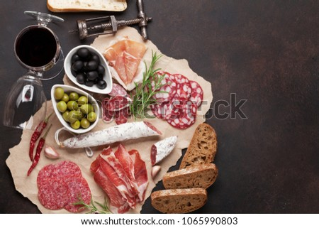 Salami, sliced ham, sausage, prosciutto, bacon, toasts, olives. Meat antipasto platter and red wine on stone table. Top view with copy space