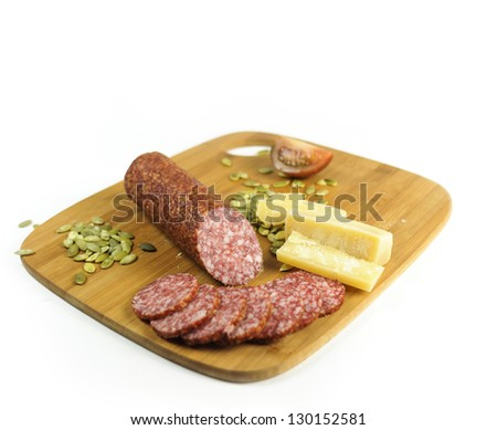 Salami with pumpkin seeds, tomatoes, cheese on the cutting board