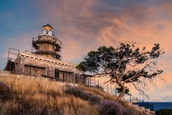 Salamis island, Greece. The stone built lighthouse at cape Koghi in Salamis island on sunset with colorful cloudy sky