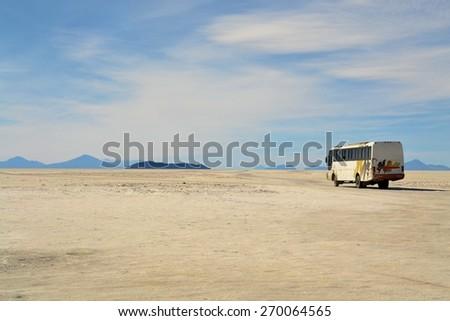 Salar Uyuni, Bolivia - 26 November 2012: A tourist bus drives through Salar Uyuni. A Jeep Tour through the Bolivian Salt Desert Uyuni is a popular touristic activity on the Altiplano in Bolivia