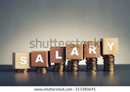 salary text written on wooden block with stacked coins on grey background