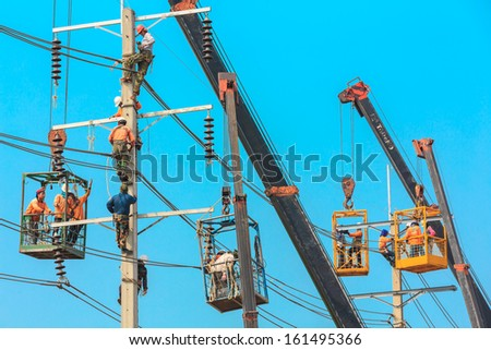 Salaya, Thailand- Oct 27:Electrician are installing high powered electric cables to cope with the increasing power usage of cities surrounding Bangkok. in Salaya Nakhonpathom Thailand on Oct 27,2013