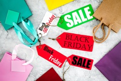 Sale and black friday labels near paper shopping bag on grey background top view