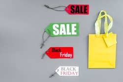 Sale and black friday labels near paper shopping bag on grey background top view copyspace