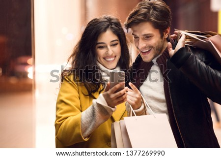 Sale and consumerism concept. Couple with shopping bags and smartphone outdoors
