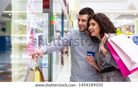 Sale and consumerism concept. Happy couple pointing finger to shop window in mall